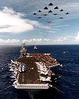 Aircraft from Carrier Air Wing 9 fly over the aircraft carrier USS John C. Stennis (CVN 74) in a delta formation.