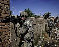A US soldier from Baker Company 2-12 Infantry Battalion aims his weapon to provide security while his comrades jump over a concrete wall to take cover in their trucks after insurgents detonated an IED or Improvised Explosive Device, 20 metres from their position during a foot patrol through the streets of the predominantly Sunni al-Dora neighborhood of southern Baghdad, 18 March 2007. US Secretary of Defense Robert Gates said today it was too soon to know whether the recent